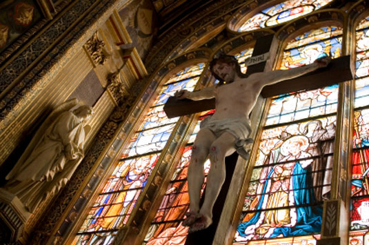 Depiction of Jesus on the cross in front of stained glass window