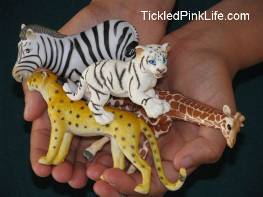Child's hands holding plastic zoo animals-used to illustrate a point about perspective