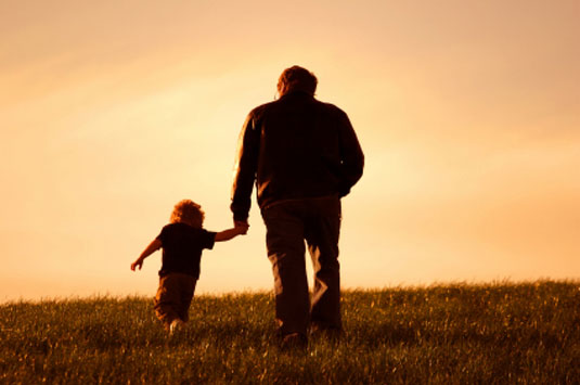 Father and child walk in the sunset